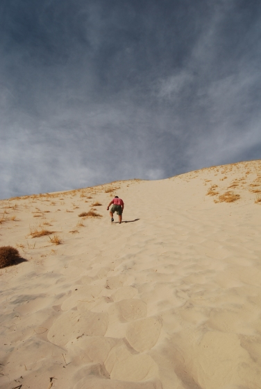 John ankle deep in soft sand- making the last slog up the sand dune.